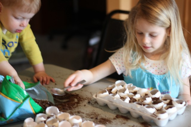 Children Adding Dirt To Eggshells